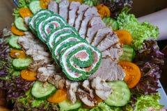Πράσινος ρόλος με τα ψάρια Ένα πιάτο με τα πράσινα και τη σαλάτα και τις κρύες περικοπές στοκ φωτογραφία
