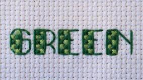 Πράσινος σταυρός που ράβεται σε πράσινο στο λευκό στοκ εικόνες