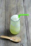 Πράσινος χυμός της Apple στο γυαλί στο ξύλινο επιτραπέζιο πάτωμα Στοκ Φωτογραφίες