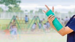 πράσινος χυτός σε διαθεσιμότητα και βραχίονας στο θολωμένο παιχνίδι σπουδαστών υποβάθρου στοκ εικόνες