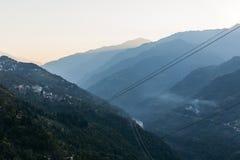 Πράσινος λόφος κοντά στο βουνό Kangchenjunga με τα σύννεφα ανωτέρω, τα δέντρα και το χωριό με το φως του ήλιου που βλέπουν το βρά Στοκ Εικόνα