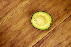 Πράσινο αβοκάντο μισό στον ξύλινο πίνακα, τοπ φωτογραφία άποψης Ενιαία φωτογραφία άποψης αβοκάντο τοπ Λαχανικό αβοκάντο περικοπών Στοκ Εικόνες