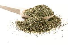 Πράσινο αλμυρό μίγμα ή Chubritsa στο ξύλινο κουτάλι στο άσπρο υπόβαθρο στοκ εικόνα