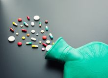 Πράσινο λαστιχένιο μπουκάλι ζεστού νερού με τα χάπια Στοκ φωτογραφία με δικαίωμα ελεύθερης χρήσης