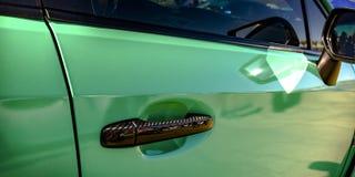 Πράσινο αυτοκίνητο με τη λαβή χαλκού και το δευτερεύοντα καθρέφτη στοκ εικόνα