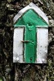 Πράσινο βέλος σημαδιών τουριστών στο δέντρο Στοκ Εικόνες