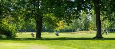Πράσινο γήπεδο του γκολφ με τους unrecognizable παίκτες γκολφ στην απόσταση, αθλητισμός στοκ εικόνες