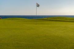 Πράσινο γκολφ με τη σημαία και τρύπα που αντιμετωπίζει τον ωκεανό Atlantico στο χρώμιο Santa Στοκ Φωτογραφία