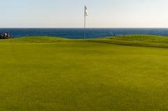 Πράσινο γκολφ με τη σημαία και τρύπα που αντιμετωπίζει τον ωκεανό Atlantico στο χρώμιο Santa Στοκ εικόνα με δικαίωμα ελεύθερης χρήσης