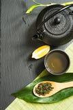 Πράσινο ιαπωνικό τσάι στο μαύρο υπόβαθρο πλακών Μαύρα teapot και κύπελλο με το πράσινο τσάι Τοπ άποψη με το διάστημα αντιγράφων Στοκ Φωτογραφία