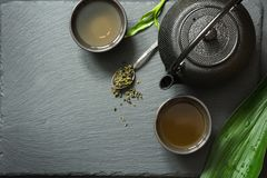 Πράσινο ιαπωνικό τσάι στο μαύρο υπόβαθρο πλακών Τοπ άποψη με το διάστημα αντιγράφων Στοκ εικόνα με δικαίωμα ελεύθερης χρήσης
