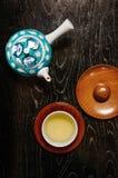 Πράσινο ιαπωνικό τσάι στο φλυτζάνι και χειροποίητο κεραμικό δοχείο στην ξύλινη ετικέττα Στοκ φωτογραφία με δικαίωμα ελεύθερης χρήσης