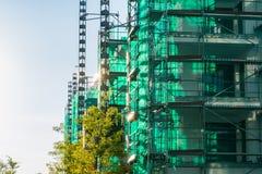 Πράσινο διαφανές καλυμμένο ηλιοβασίλεμα προγράμματος κτηρίου υλικών σκαλωσιάς Στοκ φωτογραφίες με δικαίωμα ελεύθερης χρήσης