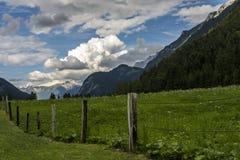 Πράσινο λιβάδι μπροστά από να απειλήσει τα σύννεφα στοκ φωτογραφίες