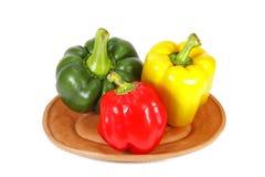 Πράσινο κίτρινο και κόκκινο γλυκό πιπέρι στο πιάτο αργίλου Στοκ Εικόνες