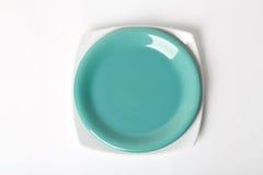 Πράσινο και άσπρο πιάτο. Στην άσπρη ανασκόπηση Στοκ Φωτογραφίες