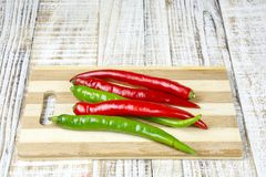Πράσινο και κόκκινο πιπέρι τσίλι που απομονώνεται σε ένα ξύλινο υπόβαθρο Στοκ Εικόνες