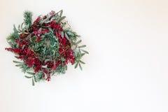 Πράσινο και κόκκινο στεφάνι σε ένα απομονωμένο άσπρο υπόβαθρο για τις διακοπές στοκ φωτογραφία