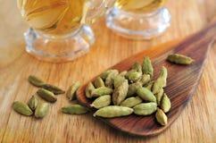Πράσινο καρδάμωμο με το πράσινο τσάι στο φλυτζάνι γυαλιών στο ξύλινο γραφείο Στοκ Φωτογραφίες