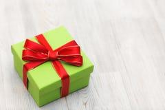 Πράσινο κιβώτιο δώρων με το κόκκινο τόξο κορδελλών που τοποθετούνται σε ένα ξύλινο υπόβαθρο Στοκ φωτογραφία με δικαίωμα ελεύθερης χρήσης