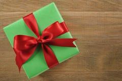 Πράσινο κιβώτιο δώρων με το κόκκινο τόξο κορδελλών στον ξύλινο δρύινο πίνακα άνωθεν Στοκ Φωτογραφία