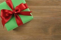 Πράσινο κιβώτιο δώρων με το κόκκινο τόξο κορδελλών στον ξύλινο δρύινο πίνακα άνωθεν Στοκ εικόνα με δικαίωμα ελεύθερης χρήσης