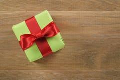 Πράσινο κιβώτιο δώρων με το κόκκινο τόξο κορδελλών στον ξύλινο δρύινο πίνακα άνωθεν Στοκ φωτογραφία με δικαίωμα ελεύθερης χρήσης