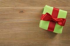 Πράσινο κιβώτιο δώρων με το κόκκινο τόξο κορδελλών στον ξύλινο δρύινο πίνακα άνωθεν Στοκ Εικόνες