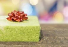 Πράσινο κιβώτιο δώρων με το κόκκινο τόξο στον ξύλινο πίνακα Στοκ εικόνα με δικαίωμα ελεύθερης χρήσης