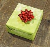 Πράσινο κιβώτιο δώρων με το κόκκινο τόξο στον ξύλινο πίνακα Στοκ Φωτογραφία