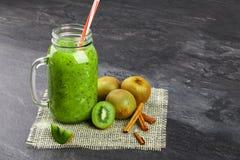 Πράσινο κοκτέιλ καταφερτζήδων σε ένα μεγάλο βάζο κτιστών Ποτό ακτινίδιων με τα φρέσκα πράσινα ακτινίδια περικοπών και κανέλα σε έ Στοκ Εικόνες