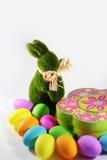 Πράσινο κουνέλι λαγουδάκι Πάσχας χλόης με ένα κιβώτιο δώρων με τα ζωηρόχρωμα αυγά Πάσχας Στοκ εικόνες με δικαίωμα ελεύθερης χρήσης