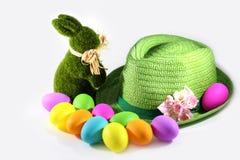 Πράσινο κουνέλι λαγουδάκι Πάσχας χλόης με ένα πράσινο καπέλο αχύρου με τα ζωηρόχρωμα αυγά Πάσχας Στοκ Εικόνα