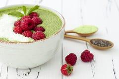 Πράσινο κύπελλο πουτίγκας σπόρου chia τσαγιού Matcha, vegan επιδόρπιο με το σμέουρο και γάλα καρύδων Η υπερυψωμένη, τοπ άποψη, επ Στοκ Εικόνες