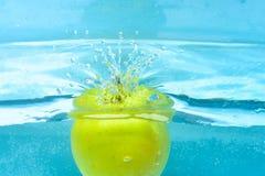 Πράσινο μήλο κάτω από το νερό με τους διαφανείς παφλασμούς φυσαλίδων και πτώσεων νερού Πλύσιμο της Apple στο καθαρό, διαφανές υγρ Στοκ φωτογραφία με δικαίωμα ελεύθερης χρήσης