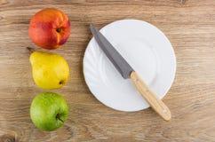 Πράσινο μήλο, κίτρινο αχλάδι και νεκταρίνι, κενά πιάτο και μαχαίρι Στοκ φωτογραφία με δικαίωμα ελεύθερης χρήσης
