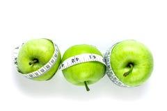 Πράσινο μήλο με τη μέτρηση της ταινίας στο άσπρο υπόβαθρο στην έννοια ο Στοκ Φωτογραφία