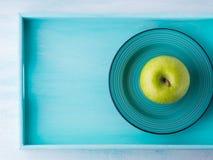 Πράσινο μήλο στο κεραμικό πιάτο στο δίσκο Στοκ Φωτογραφίες