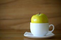 Πράσινο μήλο και άσπρο φλυτζάνι στον ξύλινο πίνακα πέρα από το ξύλινο υπόβαθρο Στοκ Φωτογραφία