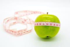 Πράσινο μήλο με να μετρήσει την ταινία γύρω Στοκ εικόνα με δικαίωμα ελεύθερης χρήσης
