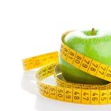 Πράσινο μήλο με τη μέτρηση της ταινίας στο λευκό Στοκ εικόνα με δικαίωμα ελεύθερης χρήσης