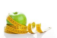 Πράσινο μήλο με τη μέτρηση της ταινίας στο λευκό Στοκ Εικόνα
