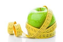 Πράσινο μήλο με τη μέτρηση της ταινίας στο λευκό Στοκ Φωτογραφία
