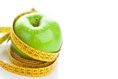 Πράσινο μήλο με τη μέτρηση της ταινίας στο λευκό Στοκ φωτογραφίες με δικαίωμα ελεύθερης χρήσης