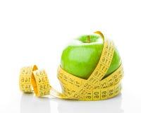 Πράσινο μήλο με τη μέτρηση της ταινίας στο λευκό Στοκ Φωτογραφίες