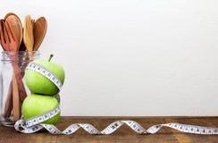 Πράσινο μήλο με τη μέτρηση της ταινίας στο ξύλινο υπόβαθρο στην έννοια Στοκ εικόνα με δικαίωμα ελεύθερης χρήσης