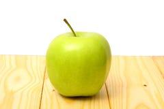 Πράσινο μήλο στον ξύλινο πίνακα Στοκ Φωτογραφίες