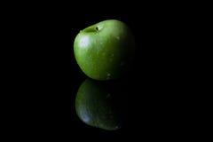 Πράσινο μήλο στο Μαύρο από την πλευρά με την αντανάκλαση Στοκ εικόνες με δικαίωμα ελεύθερης χρήσης
