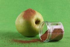 Πράσινο μήλο στο πράσινο υπόβαθρο με την κανέλα στοκ εικόνες