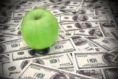 Πράσινο μήλο στο σωρό των δολαρίων Στοκ φωτογραφία με δικαίωμα ελεύθερης χρήσης